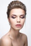 Belle fille dans une image de jeune mariée avec un paquet de cheveux et de maquillage doux Visage de beauté Photographie stock libre de droits