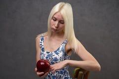 Belle fille dans une robe à la mode avec la pomme images libres de droits