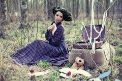 Belle fille dans une robe de plaid dans les bois Photographie stock libre de droits