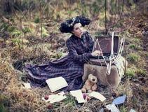 Belle fille dans une robe de plaid dans les bois Image stock