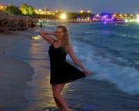 Belle fille dans une robe noire par la mer images stock