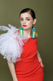 Belle fille dans une robe rouge et des boucles d'oreille des labels de caillot Images stock