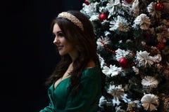 Belle fille dans une robe verte près de l'arbre de nouvelle année sur un fond noir Photos libres de droits