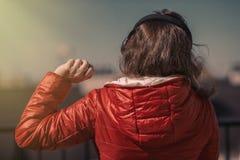 Belle fille dans une veste rouge et des écouteurs Une fille sur le balcon écoutant la musique et chante Photo stock