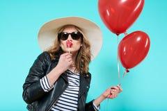 Belle fille de balancier la glace à l'eau en forme de coeur de baiser de veste en cuir et de chapeau d'été et en tenant les ballo Photographie stock libre de droits