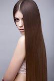 Belle fille de brune avec des cheveux parfaitement lisses et un maquillage classique Visage de beauté images stock