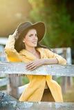 Belle fille de brune avec le regard de pays près d'une vieille barrière en bois Femme attirante avec le chapeau noir et le mantea Photos stock