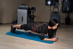 Belle fille de brune dans le costume de SME faisant l'exercice de planche sur le spor Photos libres de droits