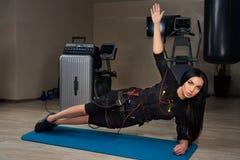 Belle fille de brune dans le costume de SME faisant l'exercice latéral de planche dessus Photos libres de droits