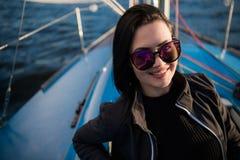Belle fille de brune dans une veste noire sur un fond et un oc?an de ciel D?placement en le bateau ou le yacht image stock