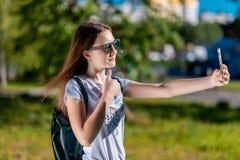 Belle fille de brune En été l'écolière est sur une coupure Dans des ses mains tient un smartphone Faites un appel visuel Prenez a Photo stock