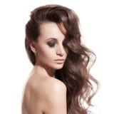 Belle fille de brune. Longs cheveux sains. Fond blanc image stock