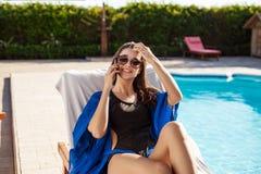 Belle fille de brune parlant du téléphone, se reposant près de la piscine Photographie stock