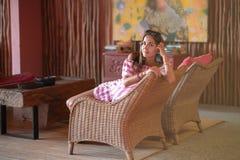 Belle fille de brune s'asseyant dans une chaise dans la moitié d'un tour Intérieur dans le style ethnique image libre de droits