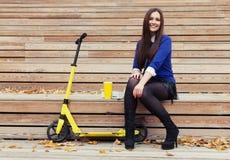 Belle fille de brune s'asseyant sur des étapes en bois avec un verre et des butées toriques Le scooter jaune se tient après Images libres de droits