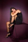 Belle fille de brunette dans la robe noire posant dedans Image libre de droits