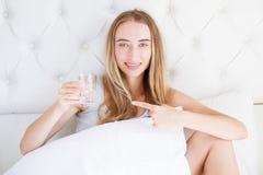 Belle fille de jeune sourire dans la chambre à coucher sur les points de lit à un verre de l'eau : perte de poids et concept de s image libre de droits