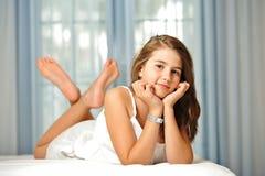 Belle fille de l'adolescence à la maison dans la robe blanche Photo stock