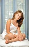 Belle fille de l'adolescence à la maison dans la robe blanche Images stock