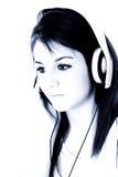 Belle fille de l'adolescence avec des écouteurs dans des sons bleus Images libres de droits