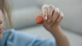 Belle fille de l'adolescence avec la fraise La belle fille de l'adolescence mange une fraise et un sourire tir de steadicam banque de vidéos