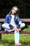 Belle fille de l'adolescence blonde dans la chemise de jeans, se reposant sur le banc avec le sac à dos et la planche à roulettes Image stock