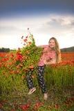 Belle fille de l'adolescence de sourire avec des fleurs de pavot Photo libre de droits
