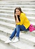 Belle fille de l'adolescence reposant sur des escaliers dans le caillot coloré Image stock