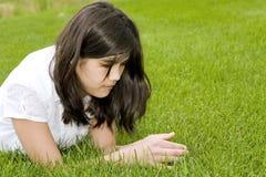Belle fille de l'adolescence se trouvant sur l'herbe Image libre de droits
