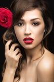 Belle fille de la manière espagnole de Carmen avec des lèvres rouges et une rose dans ses cheveux Photographie stock