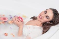 Belle fille de mannequin avec les roses roses prenant le bain de lait image libre de droits
