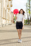 Belle fille de mode avec le ballon rouge sur la rue Photo stock