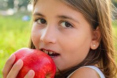 Belle fille de neuf ans mangeant la pomme image stock