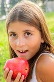 Belle fille de neuf ans mangeant la pomme Photographie stock