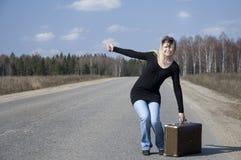 Belle fille de pays faisant de l'auto-stop sur la route Photo stock