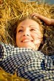 Belle fille de pays se trouvant sur la meule de foin Images stock