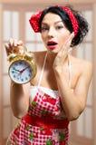 Belle fille de pin-up étonnée tenant le réveil Photo stock