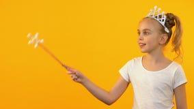 Belle fille de princesse ondulant la baguette magique magique et souriant à la caméra, enfance heureux banque de vidéos