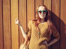 Belle fille de roux avec le grand sac à la mode dans des lunettes de soleil se tenant près du mur en bois photographie stock libre de droits