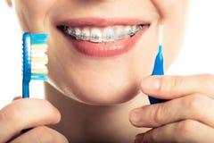 Belle fille de sourire avec l'arrêtoir pour des dents de brossage de dents photographie stock libre de droits