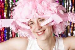 Belle fille de sourire avec la perruque du plumage rose image stock