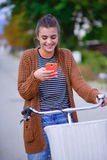 Belle fille de sourire avec une bicyclette sur la route Images libres de droits