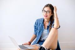 Belle fille de sourire en verres avec le tir de studio d'ordinateur portable Images stock