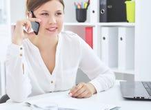 Belle fille de sourire parlant au téléphone portable se reposant au bureau photos stock
