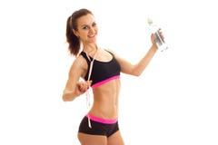 Belle fille de sport dans des sourires noirs et tenir de dessus une bouteille de l'eau et sur les épaules de la bande de mesure Photos libres de droits