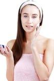 Belle fille de station thermale jugeant le pot de crème d'isolement sur le backgr blanc Photographie stock libre de droits