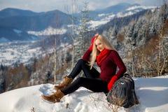 Belle fille de touristes blonde s'asseyant sur la roche photos libres de droits
