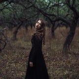 Belle fille dedans dans la robe noire de vintage avec les cheveux bouclés posant dans les bois La femme dans la rétro robe perdue photo libre de droits