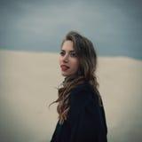 Belle fille dedans dans la robe noire de vintage avec les cheveux bouclés posant sur le sable Femme dans de rétros dres Émotion s image stock
