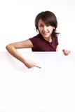 Belle fille derrière un panneau blanc vide Image stock